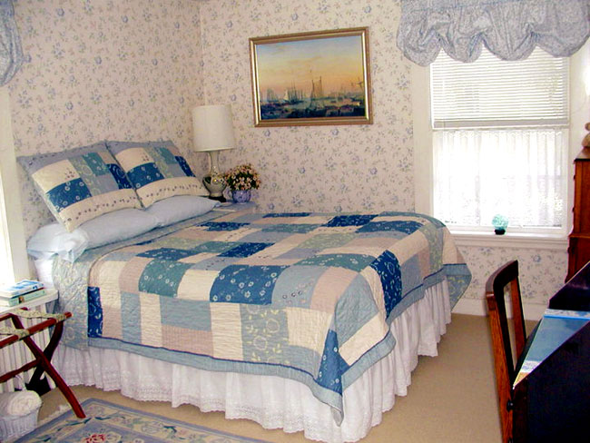 Cozy full bed with blue coloring throughout.